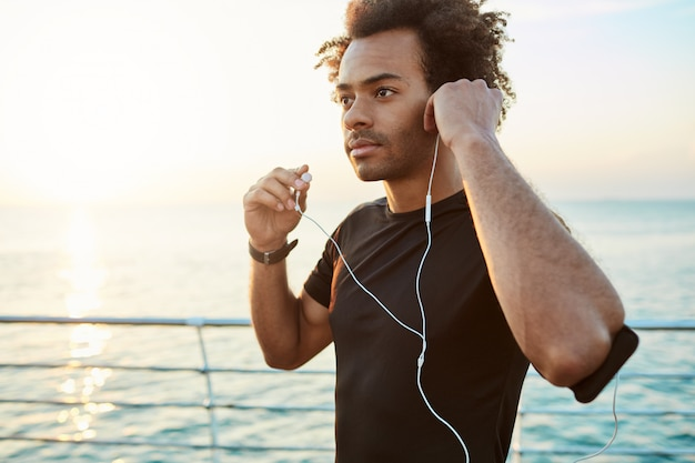 Portrait of afro-american athlete wearing white earphones, getting ready for jogging. running at the sunrise behind the sea. healthy lifestyle concept