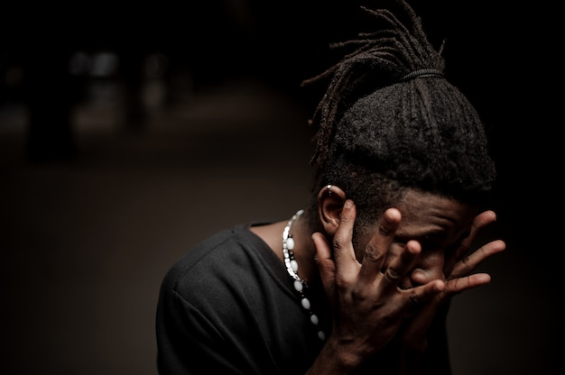 Portrait of the afro american guy with hands near his face