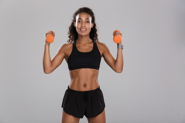 Portrait of an afro american happy sportswoman isolated over gray background, exercising with dumbbells