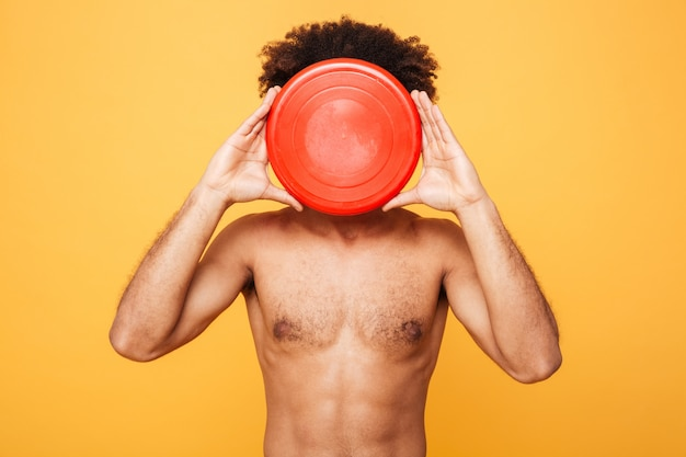 Portrait of an afro american man covering face with frisbee