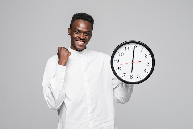 Portrait of a afro american man holding wall clock win gesture isolated on a white background