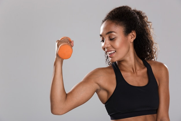 Portrait of an afro american smiling sportswoman isolated over gray background, exercising with dumbbells