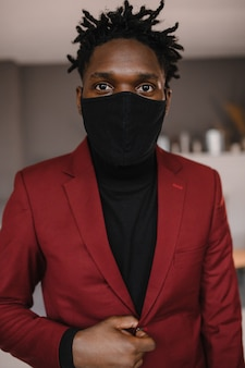 Portrait of an afro american in a suit wears a black medical mask