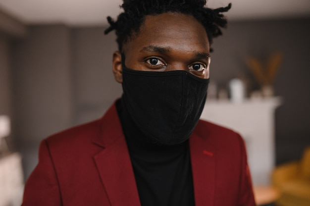 Portrait of an afro american in a suit wears a black medical mask.