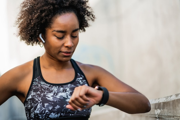 Portrait of afro athlete woman checking time on her smart watch. sport and healthy lifestyle concept.