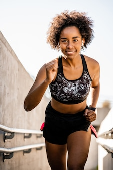 Portrait of afro athlete woman running and doing exercise outdoors. sport and healthy lifestyle.