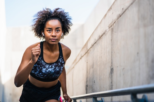 Portrait of afro athlete woman running and doing exercise outdoors