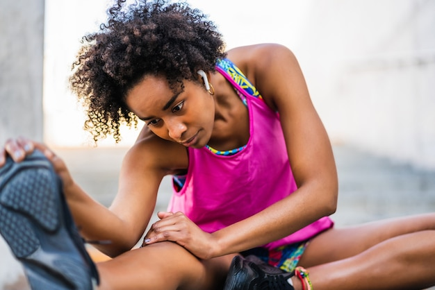 Portrait of afro athlete woman stretching legs before exercise outdoors