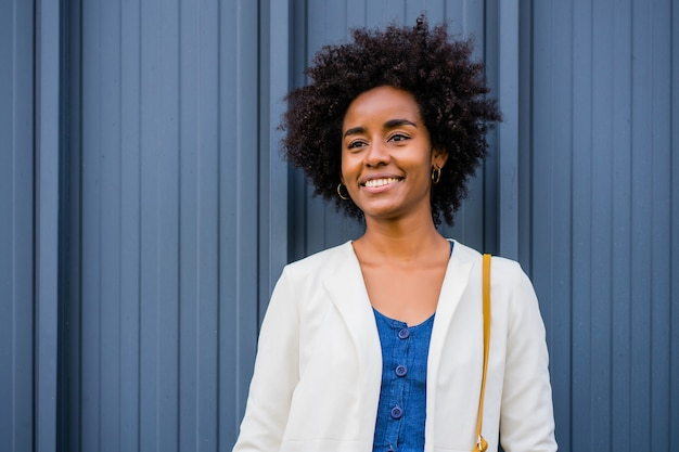 Portrait of afro business woman smiling while standing outdoors on the street. business and urban concept.