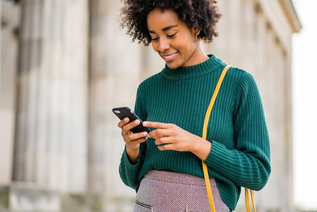 Portrait of afro business woman using her mobile phone while standing outdoors at the street