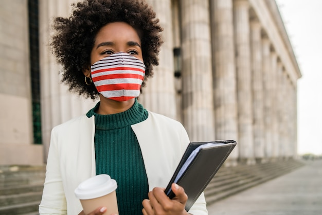 Portrait of afro businesswoman with protective mask holding a cup of coffee and clipboard while standing outdoors at the street. business concept.