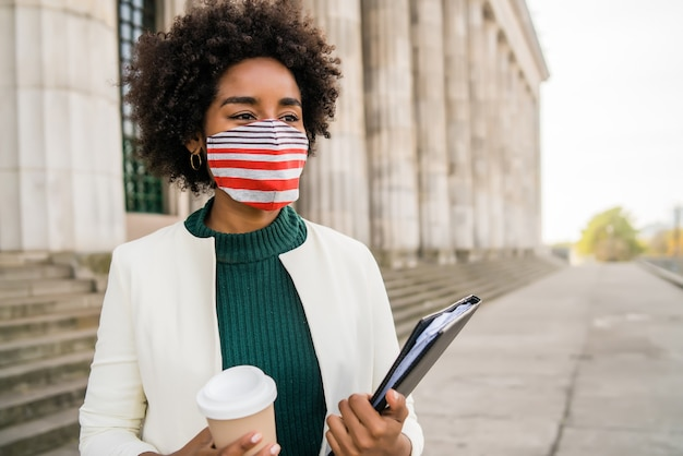 Portrait of afro businesswoman with protective mask holding a cup of coffee and clipboard