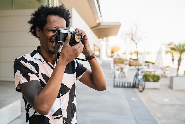 Portrait of afro man taking photographs with camera while walking outdoors on the street