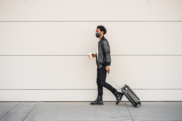 Portrait of afro tourist man carrying suitcase and holding a cup of coffee while walking outdoors on the street. tourism concept.