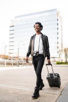 Ritratto di turista afro uomo che porta la valigia mentre si cammina all'aperto sulla strada. concetto di turismo.