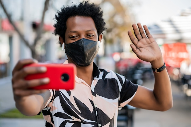 Portrait of afro tourist man doing video call on mobile phone while standing outdoors on the street. new normal life concept. tourism concept.
