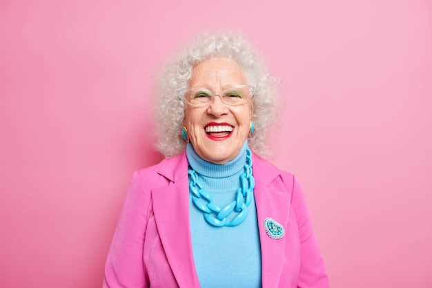 Portrait of aged beautiful woman with curly grey hair bright makeup smiles happily expresses positive emotions dressed in fashionable outfit