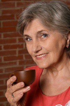 Portrait of aged woman drinking coffee on brown background