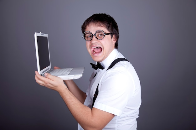 Portrait of aggressive fashion men in suspender with bow tie and glasses keeping notebook.