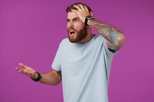 Ritratto di agitato tatuato bruna ragazzo con la barba stringendo la testa con la mano alzata e guardando da parte con la faccia confusa, isolato su viola