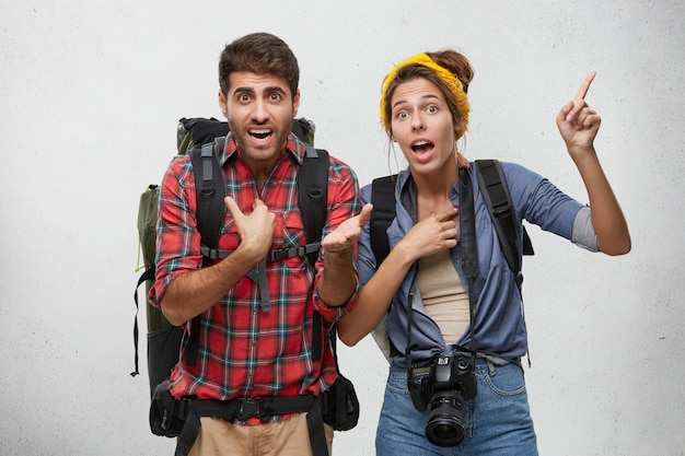 Portrait of agitated young couple with rucksacks gesturing actively, trying to explain themselves while being late for plane, looking worried. body language. tourism, travel and adventure concept