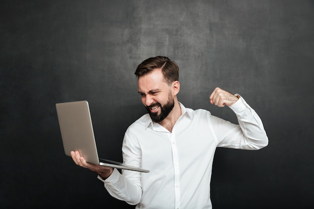 Portrait of agressive bearded man holding silver personal computer and throwing punch in screen, isolated over dark gray wall