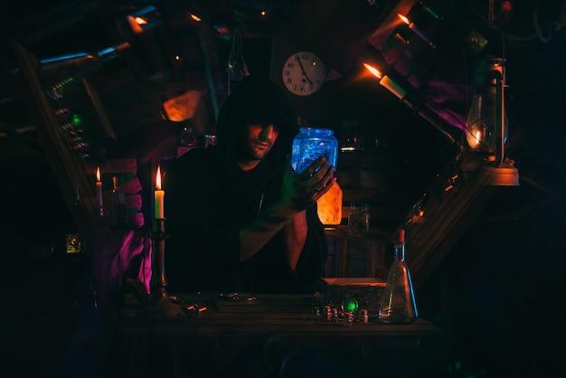Portrait of alchemist magician in interior of dark laboratory workshop with flasks and equipment. halloween cosplay