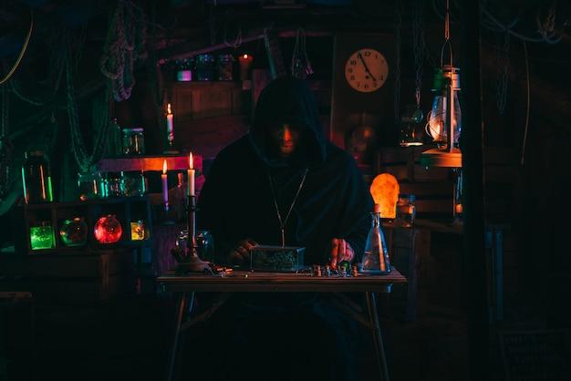 Portrait of alchemist magician in interior of dark laboratory workshop with flasks and equipment