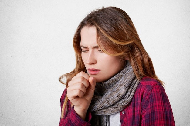 Portrait of allegic ill female has cough, caught cold, feels unhealthy, looks sick, wears warm knitted scarf on thore throat