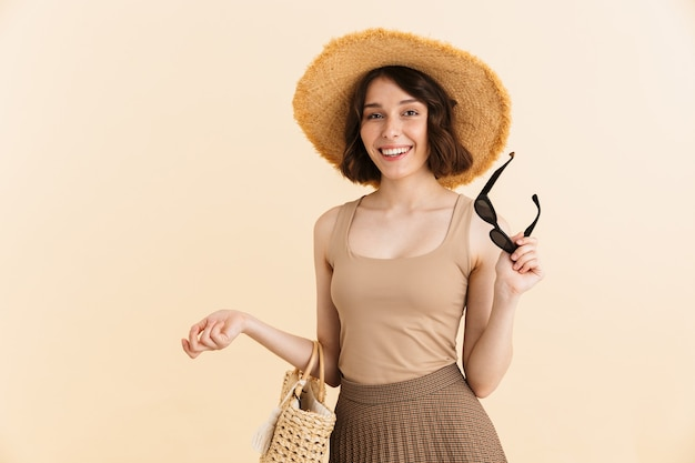 Portrait of alluring brunette woman wearing straw hat posing with summer bag and sunglasses in hand isolated