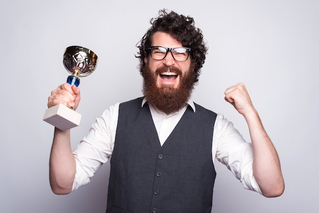 Portrait of amazed bearded hipster man in suit holding cup and celebrating.