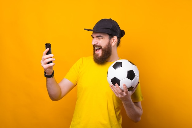 Portrait of amazed bearded young man looking at smartphone and holding soccer ball, support favorite team