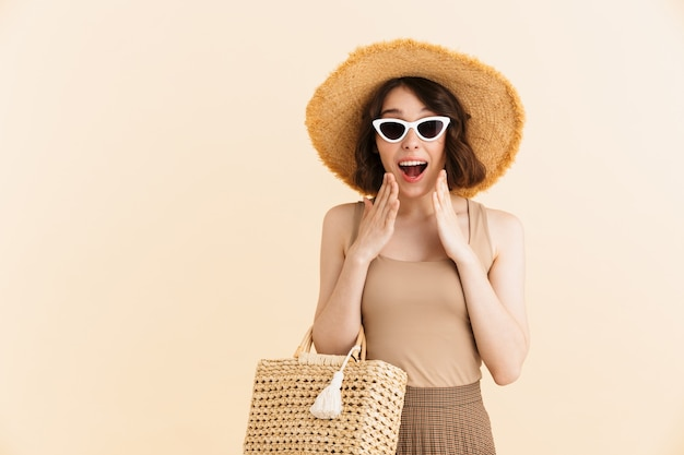 Portrait of amazed brunette woman wearing straw hat and sunglasses expressing surprise with open mouth isolated
