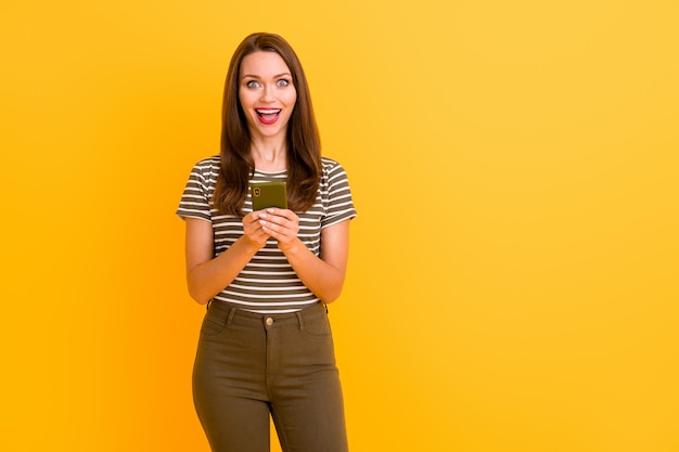 Portrait of amazed funky crazy girl use cell phone get social media notification about blog followers subscribers scream wow omg wear stylish clothes isolated over bright color wall