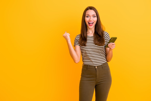 Portrait of amazed funky crazy girl use smart phone get like social media notification impressed raise fists scream wow omg wear stylish outfit isolated over shine color wall