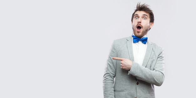 Portrait of amazed handsome bearded man in casual grey suit and blue bow tie standing looking at camera with surprised face and pointing at copyspace. studio shot, isolated on light grey background.