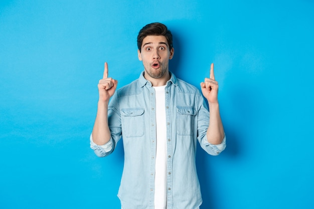 Portrait of amazed handsome man pointing fingers up, showing logo on blue background