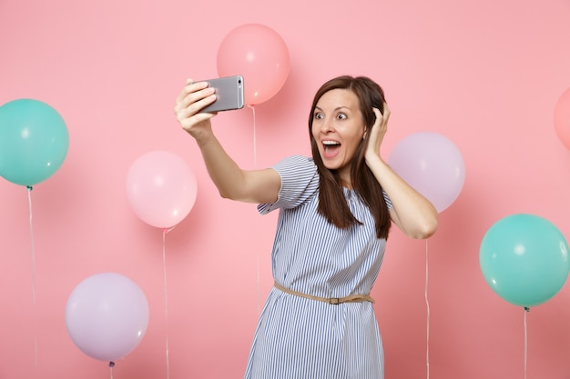 Portrait of amazed happy woman in blue dress doing selfie on mobile phone clinging to head on pastel pink background with colorful air balloons. birthday holiday party people sincere emotions concept.