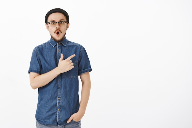 Portrait of amazed and impressed handsome young bearded guy in stylish beanie and blue shirt dropping jaw in wow sound pointing at upper right corner staring questioned and thrilled over white wall