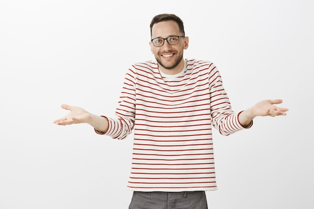 Portrait of amazed joyful handsome male with beard in glasses, shrugging and spread palms, smiling awkwadly, being carefree and relaxed after losing chance, staying on bright side over gray wall