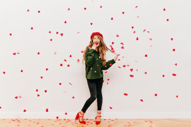 Ritratto di donna dai capelli lunghi stupita in berretto rosso divertendosi in studio
