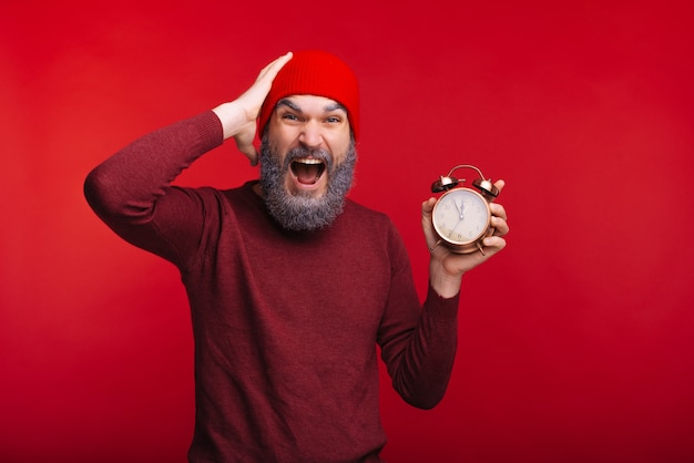 Portrait of amazed man with white beard holding alarm clock