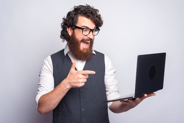 Portrait of amazed man wuith beard in suit pointing at his laptop.