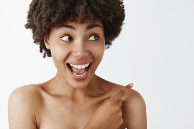 Portrait of amazed and pleased good-looking african american posing naked over gray wall, pointing and gazing right with joy over grey wall