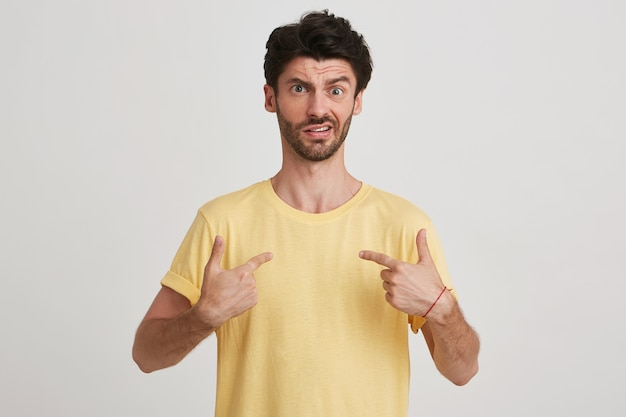 Portrait of amazed shocked bearded young man wears yellow t shirt feels astonished and points at himself with both hands isolated on white
