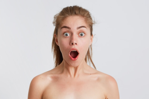 Portrait of amazed shocked naked young woman