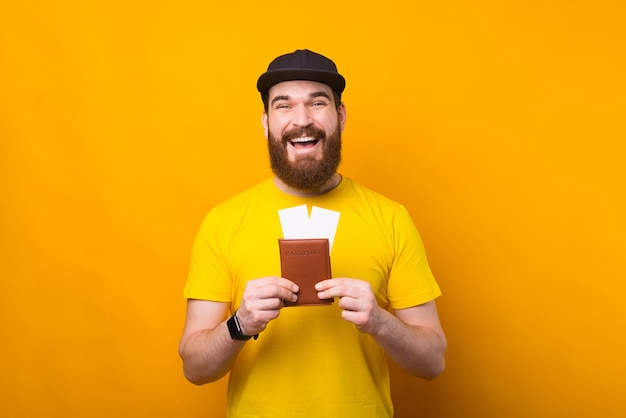 Portrait of amazed smiling man with beard holding passport and airplane tickets