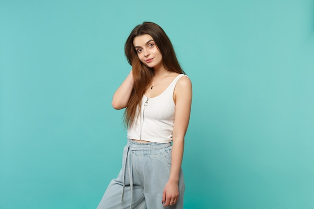 Portrait of amazed smiling young woman in light casual clothes looking camera putting hand on head isolated on blue turquoise background. people sincere emotions lifestyle concept. mock up copy space.