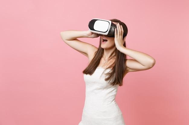 Ritratto di donna stupita in abito bianco, cuffia di realtà virtuale aggrappata alla testa