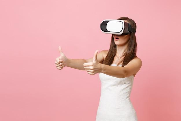 Ritratto di donna stupita in abito bianco, auricolare della realtà virtuale che mostra i pollici in su